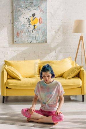 Photo pour Fille aux cheveux colorés et jambes croisées assis sur un tapis de yoga et méditant dans le salon - image libre de droit