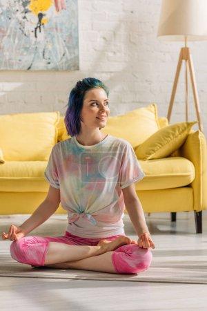 Photo pour Fille aux cheveux colorés souriant, regardant loin et méditant sur tapis de yoga dans le salon - image libre de droit