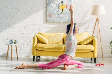 Photo pour Fille aux cheveux colorés en pose de pigeon sur tapis de yoga dans le salon - image libre de droit
