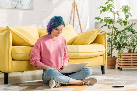 Freelancer with colorful hair working with laptop near smartphone on floor