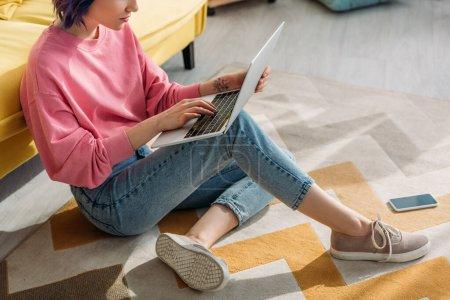 Photo pour Vue recadrée de pigiste avec des cheveux colorés travaillant avec un ordinateur portable près du canapé et smartphone sur le sol dans le salon - image libre de droit