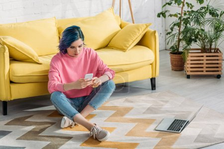 Freelancer with colorful hair and crossed legs holding smartphone on floor near sofa and laptop