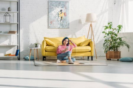 Photo for Woman with colorful hair and smartphone sitting near sofa on floor in living room - Royalty Free Image
