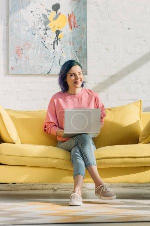 Photo pour Freelance avec des cheveux colorés et ordinateur portable souriant et assis sur un canapé avec jambes croisées dans le salon - image libre de droit