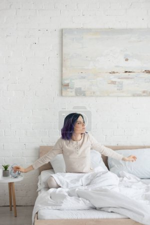 Photo for Attractive woman with colorful hair and open arms looking away on bed in bedroom - Royalty Free Image
