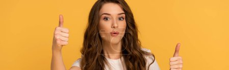 panoramic shot of beautiful surprised woman showing thumbs up isolated on yellow