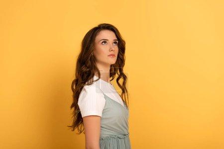 Photo pour Attrayante jeune fille pensive en t-shirt et en robe jaune - image libre de droit