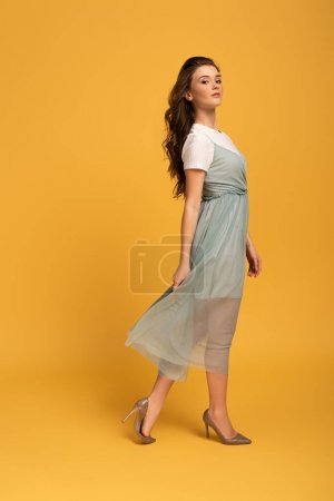 attractive young spring woman in elegant dress on yellow
