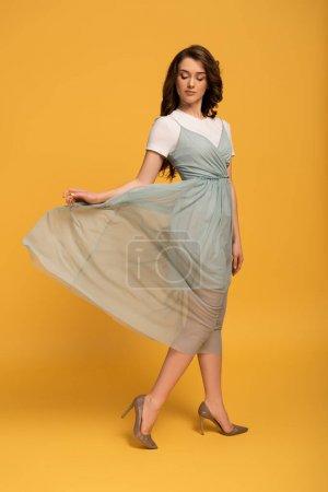 Photo pour Tendre jeune femme de printemps en robe élégante sur jaune - image libre de droit