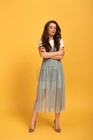 Photo pour Tendres jeune femme printanière aux cheveux longs et aux bras croisés en jaune - image libre de droit
