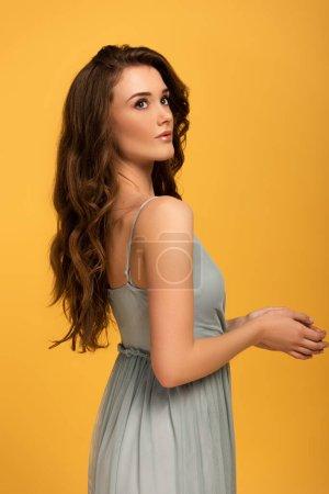Photo pour Élégante fille de printemps avec les cheveux longs en robe isolé sur jaune - image libre de droit