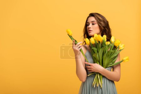 Photo for Beautiful girl in spring dress holding tulip flowers isolated on yellow - Royalty Free Image