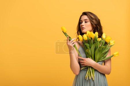 Photo pour Belle fille en robe de printemps tenant des fleurs de tulipes isolées sur jaune - image libre de droit