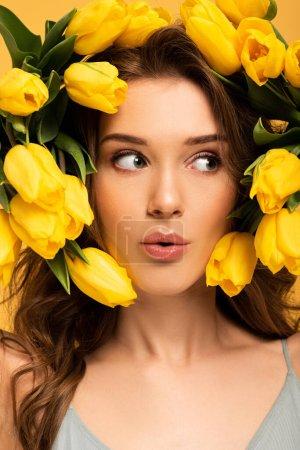 hermosa chica sorprendida en flores frescas de tulipán aislado en amarillo