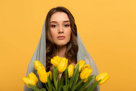 Photo for Attractive young woman in veil holding bouquet of tulips isolated on yellow - Royalty Free Image
