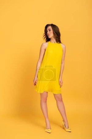 Photo pour Attrayant élégant jeune femme en robe sur jaune - image libre de droit