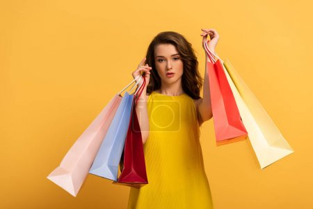 Photo for Beautiful elegant girl in spring dress holding shopping bags on yellow - Royalty Free Image