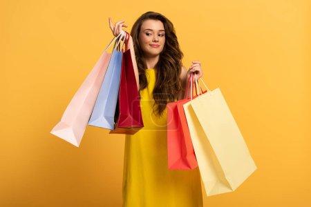 Photo pour Belle fille souriante en robe de printemps tenant des sacs à provisions sur jaune - image libre de droit