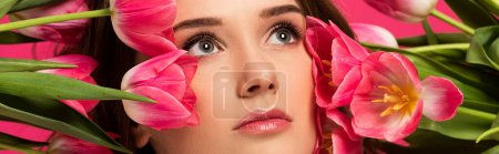 Photo for Panoramic shot of beautiful girl with spring tulip flowers isolated on pink - Royalty Free Image