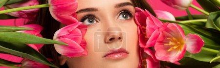 Photo pour Plan panoramique de belle fille avec des fleurs de tulipe de printemps isolé sur rose - image libre de droit