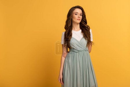 Photo for Tender pretty girl in t-shirt and dress on yellow - Royalty Free Image