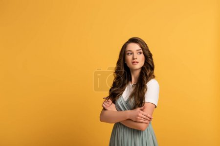 Photo for Attractive thoughtful girl with crossed arms on yellow - Royalty Free Image