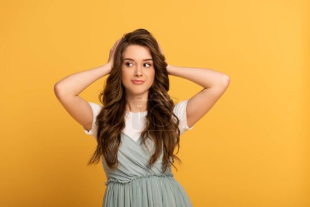 Photo for Smiling spring girl with long hair on yellow - Royalty Free Image