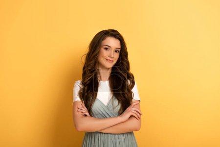 Photo pour Attrayant souriant printemps fille avec les bras croisés sur jaune - image libre de droit