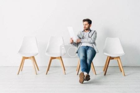 Handsome man looking at resume while sitting on chair in office