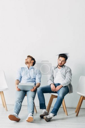 Photo for Tired applicants with resume and laptop sitting on chairs in office - Royalty Free Image