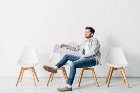 Foto de Vista lateral del hombre con curriculum vitae sentado en la silla en la oficina - Imagen libre de derechos