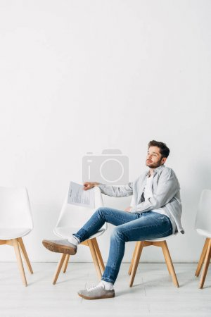 Handsome candidate with resume sitting on chair in office