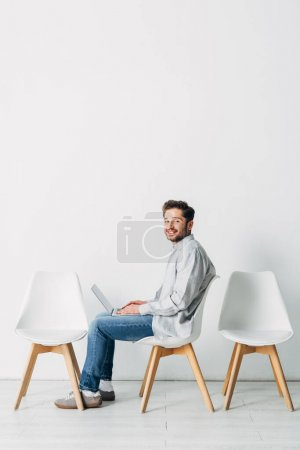 Side view of smiling employee using laptop while waiting for job interview