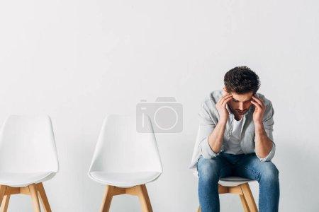 Foto de El hombre reflexivo que espera la entrevista de trabajo en la silla en la oficina - Imagen libre de derechos