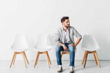 Un empleado guapo mirando hacia otro lado mientras está sentado en la silla en la oficina