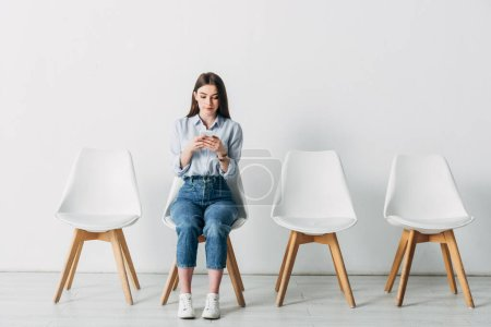 Photo pour Jeune femme utilisant un téléphone intelligent en attendant l'entrevue d'emploi au bureau - image libre de droit