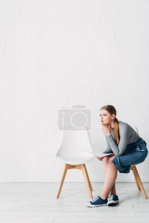 Photo pour Vue latérale de la femme avec CV regardant loin sur la chaise dans le bureau - image libre de droit