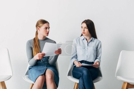 Photo for Stressed employee looking at young woman with resume in office - Royalty Free Image