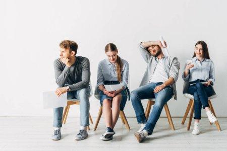 Foto de Grupo de empleados con curriculum vitae sentado en sillas en la oficina - Imagen libre de derechos