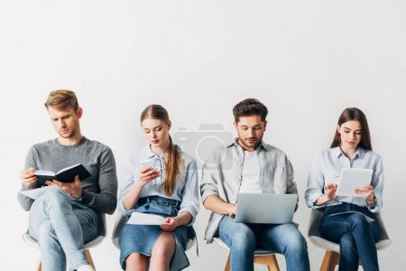 Photo for Employees using digital devices while waiting for job interview in office - Royalty Free Image