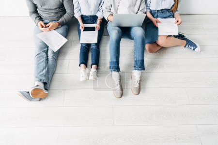 Photo for Cropped view of employees with resume and digital devices sitting on floor in office - Royalty Free Image