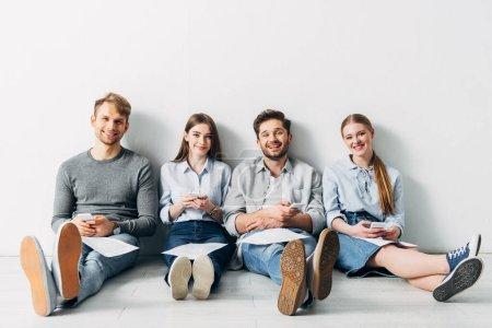 Photo pour Groupe de jeunes candidats avec CV et smartphones souriant à la caméra sur le sol - image libre de droit