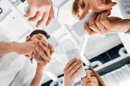Photo pour Vue du bas des jeunes utilisant des smartphones au bureau - image libre de droit