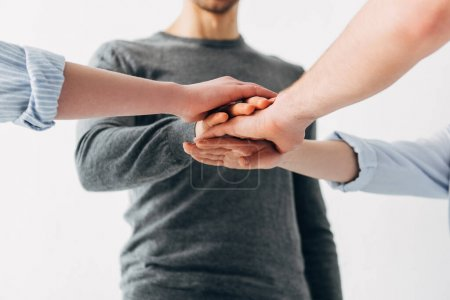 Photo for Cropped view of coworkers holding hands in office - Royalty Free Image