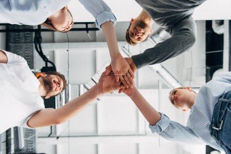 Foto de Vista inferior de compañeros de trabajo sonrientes mirándose mientras se toman de la mano en la oficina - Imagen libre de derechos