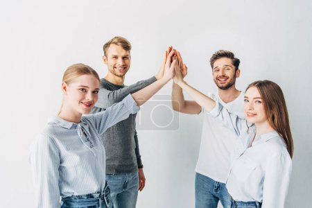 Photo for Young coworkers smiling at camera while high five in office - Royalty Free Image