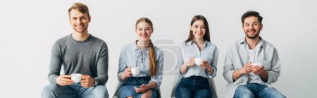 Photo for Panoramic shot of coworkers with cups smiling at camera - Royalty Free Image