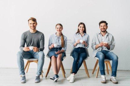 Photo pour Travailleurs souriants avec des tasses à café souriant à la caméra sur des chaises dans le bureau - image libre de droit