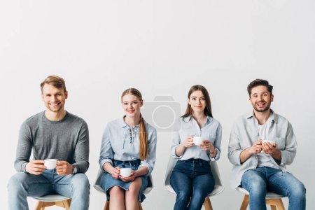 Foto de Compañeros alegres sonriendo a la cámara mientras beben café juntos - Imagen libre de derechos