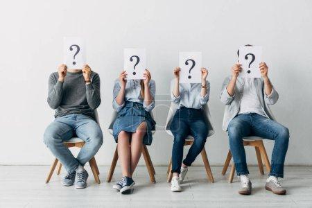 Photo pour Jeunes détenteurs de cartes avec points d'interrogation en attente d'un entretien d'embauche - image libre de droit